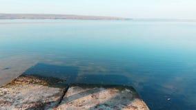 Drohnenfliegen über Steinplatten und Start über blauem Fluss Szenischer steigender Start über See Reise und Hereinkommen stock video footage