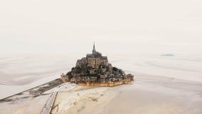 Drohnenfliegen gelassen über Mont Saint Michel-Insel mit Abtei und Straße mit Touristen während der Ebbe an einem nebelhaften Tag stock video footage