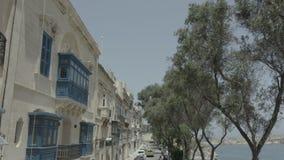 Drohnenfliegen zurück durch schöne alte Straße, nah an Meer in Valletta, Malta Alt, Weinlesefenster, Balkone - 4K stock video