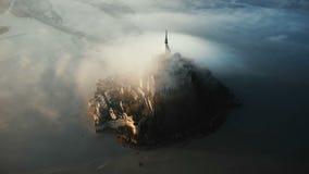 Drohnenfliegenhoch um die erstaunliche Mont Saint Michel-Inselschlossfestung bedeckt mit enormem Sonnenaufgangnebel-Wolkenfluß stock footage