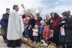 Drohobych, de Westelijke Oekraïne - April 08, 2017: De priester zegent Pasen-manden met heilig water stock foto's