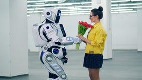 Droid дает красные тюльпаны девушке и она обнимает ее сток-видео