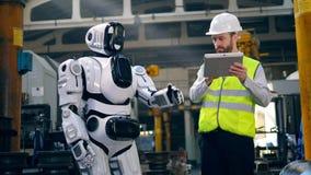 Droid est contrôlé par un travailleur et des mains de levage banque de vidéos