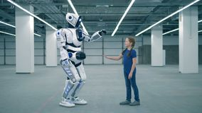 Droid and girl touch hands, side view. School kid, education, science class concept. A robot and a child touching hands stock footage