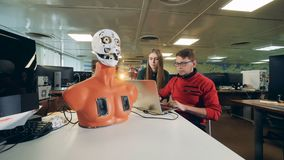 Droid que controla en un laboratorio, cierre de la mujer y del hombre para arriba almacen de video