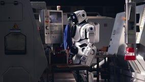 Droid trabaja con la máquina industrial, botones que empujan almacen de video