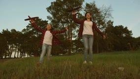 Dromen van het Vliegen Gelukkig kinderjarenconcept Twee meisjes spelen met een stuk speelgoed vliegtuig bij zonsondergang Kindere stock video