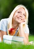 Dromende vrouw die op het gras dichtbij de stapel van boeken liggen Stock Foto