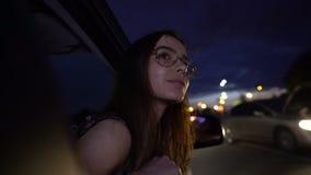 Dromerig donkerbruin plakkend hoofd uit auto, die van nacht genieten, onbezorgd en geïnspireerd stock videobeelden