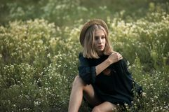 Dromerig jong meisje in een strohoed en zwarte kledingszitting in F stock afbeeldingen
