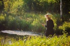 Dromerig kindmeisje op de zomergang op rivieroever Comfortabele landelijke scène Openlucht activiteiten Royalty-vrije Stock Afbeelding