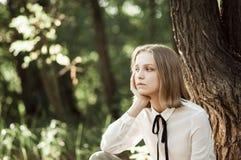 Dromerig tienermeisje in witte blouse met zwart lint stock foto's