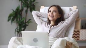 Dromerige meisjeszitting als voorzitter die thuis met laptop rusten stock footage