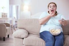 Dromerige red-head vrouw die popcorn op de laag eten royalty-vrije stock foto