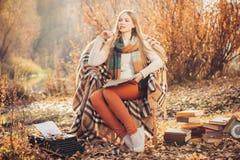 Dromerige vrouw die in het de herfstpark schrijven Stock Foto's