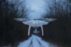 Dron flying midair from behind. Photo of drone Phantom 4 from behind flying over the small path royalty free stock photos