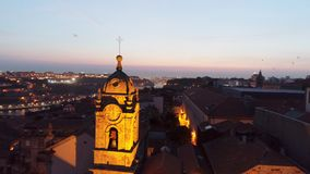 Dron flying near lighted belfry in Porto at dusk. Motion shot dron flying near lighted belfry with clock in historic center of european city. Aerial view Porto stock video