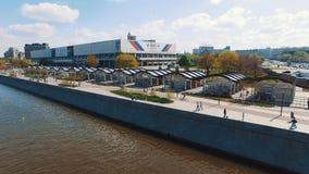 Dron ha sparato del fiume della città, la gente che cammina sul embankmet, sport che costruiscono nel parco archivi video