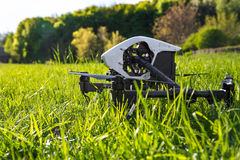 Dron is located in the green grass before takeoff. Copter engine is not running. Low point shooting, close-up Stock Photo