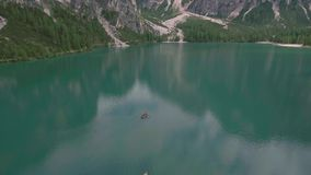 Drone aerial flying over a scenic Lago di Braies with boats in Dolomites Alps stock footage