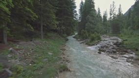 Drone aerial flying over a wild mountain river with woman on the bridge in Dolomites Alps. Drone aerial flying over a wild mountain river with woman on the stock video footage