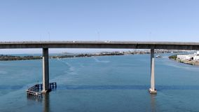Aerial of flying under bridge in coastal city stock footage