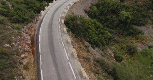 Drone aerial following a car through mountain road. B roll image made on drone quickly flies above curved and scenic mountain road with small white car driving stock footage