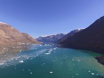 Drone aerial image of icebergs and turbid glacial runoff in a narrow fjord in Northeast Greenland. Drone image acquired at the terminus of a glacier during a royalty free stock photos
