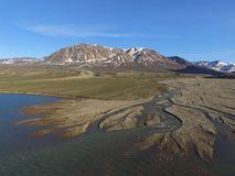Drone aerial image of snow melt fed streams in a fluvial river valley entering a fjord in northeast Greenland. Drone aerial image acquired during a research royalty free stock photo