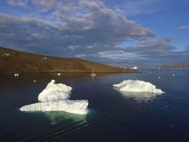 Drone aerial image of two large icebergs with a sailboat at anchor in western Greenland. Drone aerial image taken during a sailing expedition to western stock photos