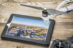 Drone aerial photography concept. Reviewing aerial pictures of Fort Collins downtown on a digital tablet with a drone rotor and radio control transmitter stock images