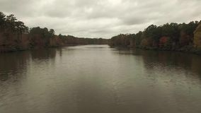 Drone Aerial Video of fishermen in a boat. Drone Aerial video of a lake, boat with two men fishing, foliage, still water and trees near Raleigh, NC stock footage