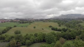 Drone aerial view above hills and forests and large green meadows