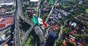 Drone-aerial view of a huge mexican flag fluttering, just outside Mexico City. A highway and some suburbs in the back. TAKE 2 stock footage