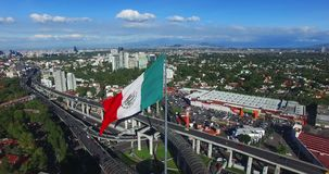 Drone aerial view of a huge Mexican flag waving. In the back, panoramic view of Mexico City. Many cars transit for the avenue.