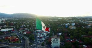 Drone-Aerial view of a huge mexican flag waving, at back the sun is hiding behind the mountains. Many cars transit for the avenue. stock video footage