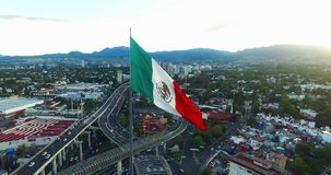 Drone-Aerial view of a huge mexican flag waving, at back the sun is hiding behind the mountains. Many cars transit for the avenue.