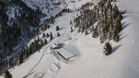 Drone aerial view of the lodge Cassinelli after a snow fall. Italian Alps.  Royalty Free Stock Images