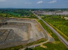 Drone view of opencast mining quarry in the middle of the forest landscape