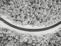 Drone aerial view of road in the snowy forest royalty free stock photos