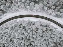 Drone aerial view of road in the snowy forest Stock Photos