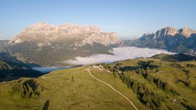 Drone aerial view at Sella mountain range. Fog at the bottom of the valley. Alta Badia, Sud Tirol, Dolomites, Italy. Summer time stock image