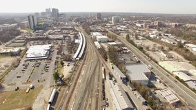Drone Aerial View of Skyline, Train Tracks and Highway North Raleigh, NC. Drone aerial view of skyline and train tracks near an Industrial area of Raleigh, NC stock footage