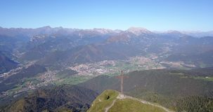 Drone aerial view to the Seriana valley and Orobie Alps in a clear and blue day. The cross at the top of the mountain. Landscape from Pizzo Formico Mountain stock footage