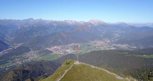 Drone aerial view to the Seriana valley and Orobie Alps in a clear and blue day. The cross at the top of the mountain. Landscape from Pizzo Formico Mountain stock video