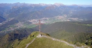 Drone aerial view to the Seriana valley and Orobie Alps in a clear and blue day. The cross at the top of the mountain. Landscape from Pizzo Formico Mountain stock video footage