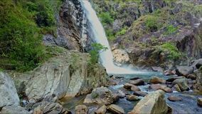 Drone Approaches along River and Lake to Waterfall among Rocks. Drone approaches along river and lake to strong foamy waterfall among massive forestry brown stock footage