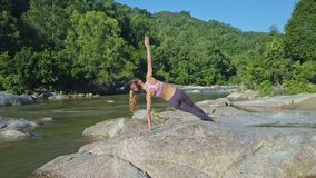 Drone Approaches Girl Doing Yoga against Tropical Plants. Drone approaches athletic girl doing yoga in Vasisthasana pose on rocks against tropical plants in stock footage