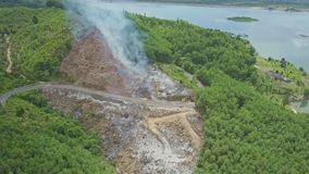 Drone approaches smoke spreading among plants against lake stock video footage