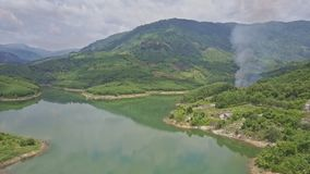 Drone approaches green hills behind lake with controlled fire. Drone approaches green hills behind lake with cultivated paper production forests and controlled